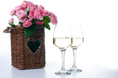 Two glasses of white wine and roses Stock Photos