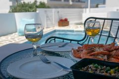 Two glasses of white wine and shrimps on the table by the pool royalty free stock photo