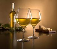 White wine in stemmed glasses. Two glasses of white wine with a bottle of wine and cheese on a wood table stock photo