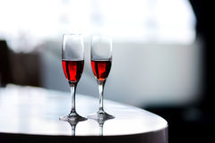 Two glasses of wine or another alcoholic beverage on a table Royalty Free Stock Photography