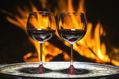 Two glasses of wine on the background of fire Stock Image