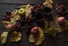 Two glasses with wine, apples and grapes on wooden surface Royalty Free Stock Images