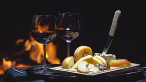 Two glasses of wine on the background of fire. On dark background stock video footage