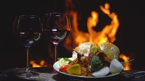 Two glasses of wine on the background of fire. On dark background stock video