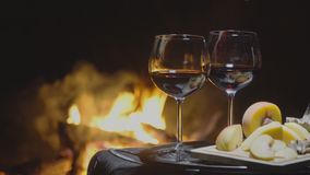 Two glasses of wine on the background of fire. On dark background stock footage