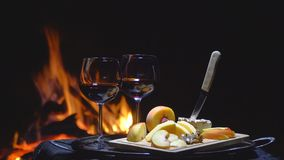 Two glasses of wine on the background of fire stock footage