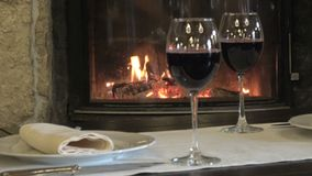 Two glasses of wine on the background of the fireplace. Two glasses of red wine on the background of a burning fire in the fireplace stock video