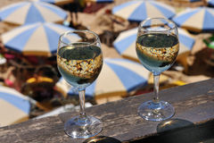 Two glasses of wine on the background of parasols Stock Photography