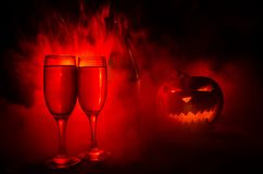 Two glasses of wine and bottle with Halloween - old jack-o-lantern on dark toned foggy background. Scary Halloween pumpkin. Useful Stock Photo