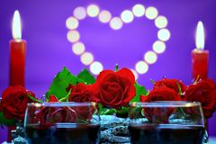 Moody decoration for Valentine`s day concept. Two glasses of wine,bouquet of roses and candles on a ultra violet background with heart Royalty Free Stock Images