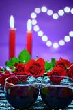 Moody decoration for Valentine`s day concept. Two glasses of wine,bouquet of roses and candles on a ultra violet background with heart Stock Images
