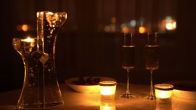 Two glasses of wine and candles in the dark with city lights at the background.  stock video