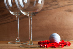 Two glasses  of wine and golf equipments Stock Photos