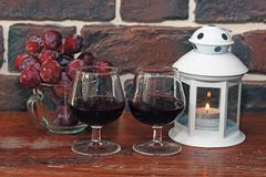 Two glasses of wine with grapes and candles royalty free stock images