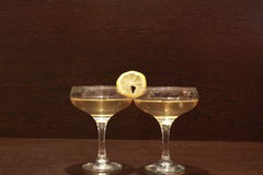 Two glasses of wine and lemon. On a dark table royalty free stock photo
