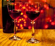 Two glasses of wine with lights in the background. Two glasses of red wine with a bottle on wooden table with red lights in the background Royalty Free Stock Images