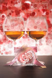 Two glasses of wine and pink heart with love on bokeh background. Stock Image