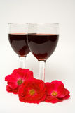 Two glasses of wine with red flowers. Roses decorated two glasses of wine, still life with wine and red roses Royalty Free Stock Image