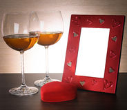 Two glasses of wine, red heart and photo frame. Royalty Free Stock Photo
