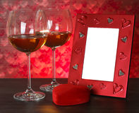 Two glasses of wine, red heart and photo frame. Stock Photography
