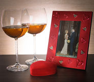Two glasses of wine, red heart and photo frame. Stock Photos