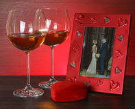 Two glasses of wine, red heart and photo frame. Stock Image