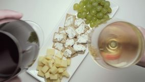 Two glasses of wine, red and white, with snacks. Top view. Male and female hands clink glasses with red and white wine. Top view stock video footage