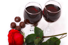 Two glasses of wine with rose and candy Stock Images