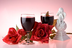 Two glasses of wine, rose and cupid. Royalty Free Stock Photo