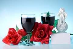 Two glasses of wine, rose and cupid. Stock Photos