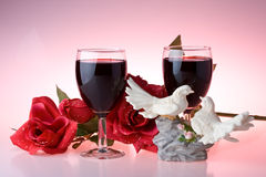 Two glasses of wine, rose and figurine Stock Image