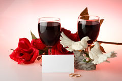 Two glasses of wine, rose and figurine Royalty Free Stock Photography