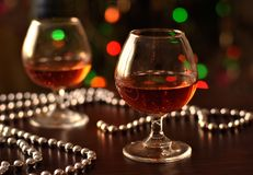 A glass of wine and silver beads on a Christmas tree background. royalty free stock photos