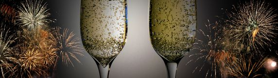 Two glasses of champagne with bubbles close-up on the background of colorful fireworks royalty free stock photography