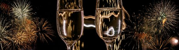 Two glasses of champagne with bubbles close-up on the background of colorful fireworks royalty free stock photos
