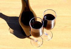 Two glasses of wine stand on a table under direct sunlight stock image