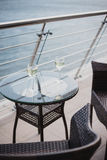 Two glasses of wine standing on on a balcony with a view at the ocean Stock Photo