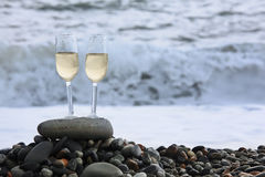 Two glasses of wine on stony beach Stock Photography