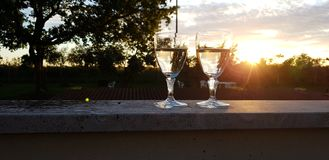 Two glasses of wine on sunset royalty free stock image