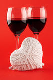 Two glasses of wine and a white heart made of wool Stock Photos