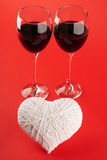 Two glasses of wine and a white heart made of wool Stock Images
