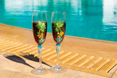 Two glasses with wine on a white table near the pool. Royalty Free Stock Images