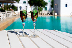 Two glasses with wine on a white table near the pool. Holiday season, It`s time to travel. Two glasses with wine on a white table near the pool.loving couple Royalty Free Stock Image