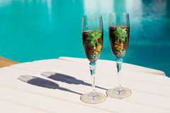 Two glasses with wine on a white table near the pool. Holiday season, It`s time to travel. Two glasses with wine on a white table near the pool.loving couple Stock Photos