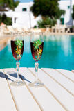 Two glasses with wine on a white table near the pool. Holiday season, It`s time to travel. Two glasses with wine on a white table near the pool.loving couple Stock Photo