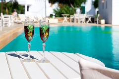Two glasses with wine on a white table near the pool. Holiday season, It`s time to travel. Two glasses with wine on a white table near the pool.loving couple Royalty Free Stock Photos