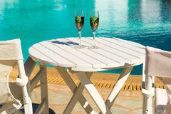 Two glasses with wine on a white table near the pool. Holiday season, It`s time to travel. Two glasses with wine on a white table near the pool.loving couple Stock Images
