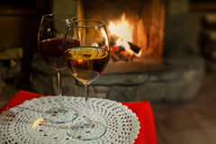 Two glasses of wine on white tablecloth. Fireplace chimney background. Romantic cozy interior. Soft background photo stock photo