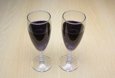 Two glasses of wine on a wooden background stock photo