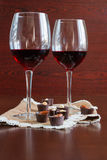Two glasses of wine on a wooden table.  Candies. Stock Image